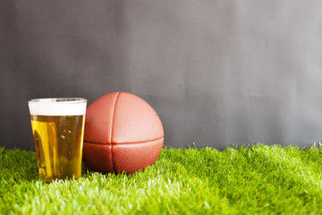 Vintage football and beer glass over grass and black background