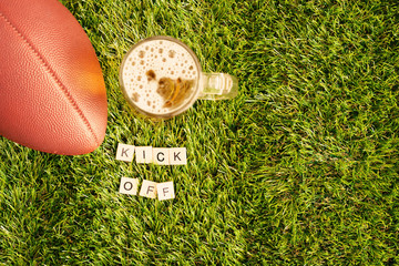 Vintage football and beer jar over grass with Kick Off message in wood tiles