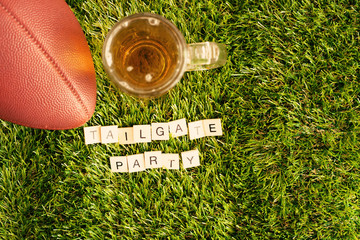 Vintage football and beer jar over grass with Tailgate Party message in wood tiles