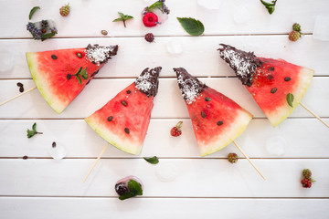 Watermelon slice popsicles on white wooden table with ice and berries Overhead view