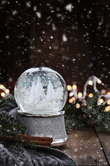 Silver Snow globe surrounded by pine branches, cinnamon sticks and a warm gray scarf with gently falling snow flakes against a rustic background.