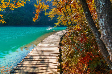 Autumn view of Plitvice Lakes National Park, tourist route on the wooden flooring along the water, Croatia
