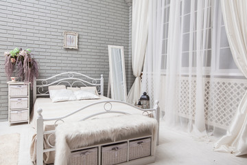 Evening bedroom with a white bed, big mirror near the window at