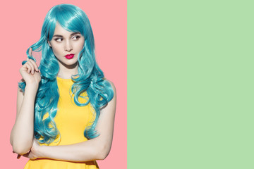 Pop art woman portrait wearing blue curly wig and bright yellow