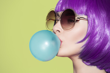 Pop art woman portrait wearing purple wig. Blow a blue bubble ch
