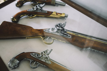 Old vintage wooden guns on a showercase