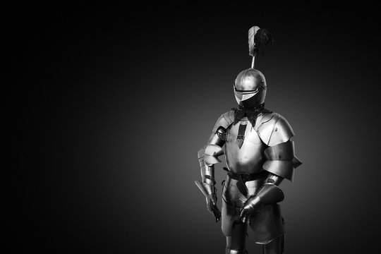 Old metal knight armour on black background