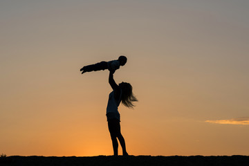 Beautiful end to an amazing day. Silhouette of mother with her child against a sunset