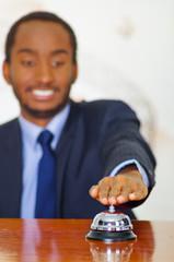 Man wearing elegant blue suit pressing desk bell at hotel reception