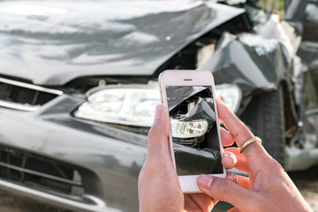 Hands of a man holding a smartphone and take pictures of a car a