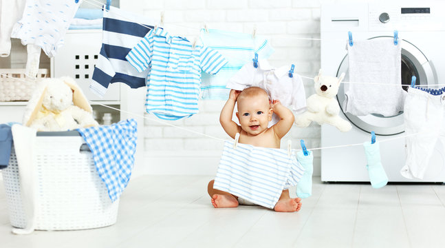 fun happy baby boy  to wash clothes and laughs in laundry