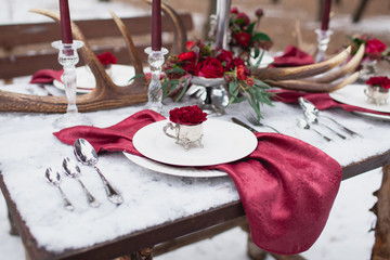 Table setting in red marsala and white colors decorated with candles, napkins, flowers, leaves, horns on wooden table made of pine in winter forest.