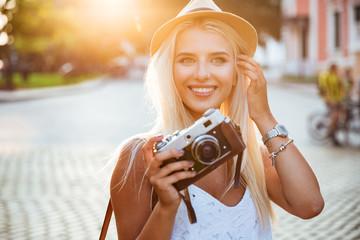 Close up portrait of a smiling girl holding retro camera