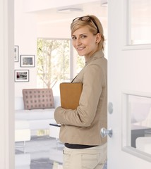 Happy businesswoman standing at home doorway