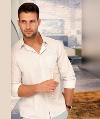 Handsome man with a glass of champagne at home