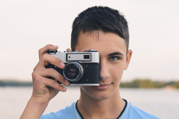 Cute boy teenager with vintage rangefinder camera.