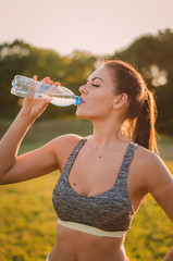 Fitness beautiful woman drinking water and sweating after exerci