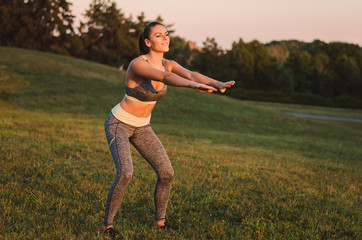Attractive fitness woman practicing in the park on the grass. Sh