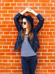 Fashion pretty woman model in black rock style posing over brick