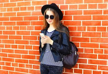 Fashion pretty woman using smartphone in rock black style over b