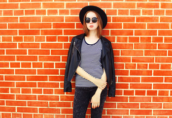 Fashion woman model in black rock style over bricks background