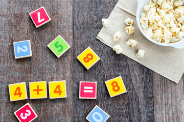Wooden Toy Plate With Numbers And Popcorn on table.
