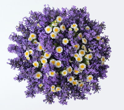Top view of a bouquet of lavender and camomile flowers on a white background. Colorful summer bouquet of purple lavandula and yellow chamomile flowers. Photo from above.