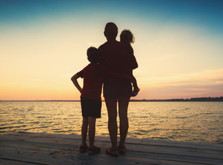 Silhouette of family watching sea sunset