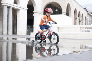 little boy riding a bike on the square