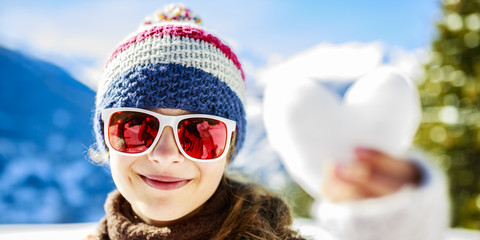 I love winter, smiling teenager holdin heart of snow.