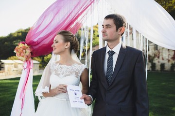 Bride and her husband are holding marriage certificate