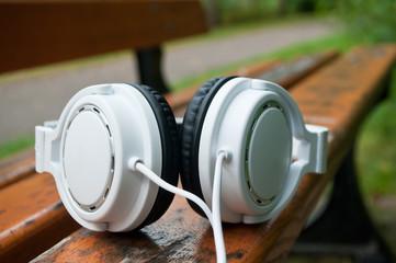 Casque audio blanc posés sur un banc en extérieur