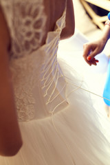 Bridesmaid tying bow on wedding dress. Closeup toned photo of beautiful bride tying up her wedding dress.