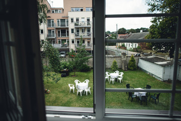 many white and black  tables facing the green courtyard