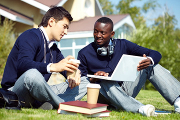 Two young students sitting in campus, drinking coffee and communicating