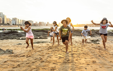 Kids running on the beach at sunset