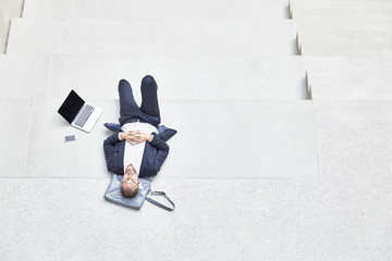 Businesssman lying on stairs next to laptop and cell phone