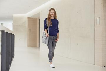 Young woman walking along corridor