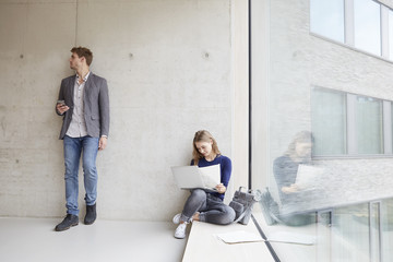 Young woman with papers and laptop and man with cell phone at concrete wall