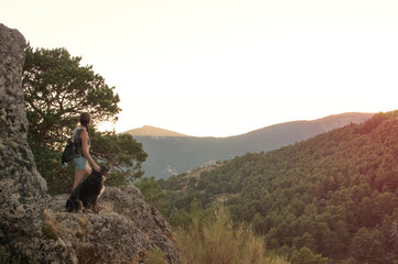 Young woman with her dog at sunset