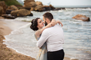 Wedding. Wedding by the sea. Young couple in love, bearded groom and bride in wedding dress at the seaside. Couple in love walking around the sea and the rocks near the place of the wedding ceremony