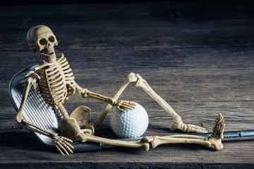 skeleton sitting with golf equipment on old wood