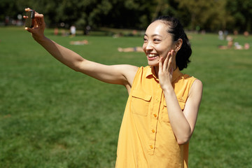 Asian woman in a city park talking selfie photo