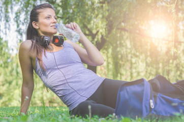 Tired woman runner taking a rest after run, drinking water