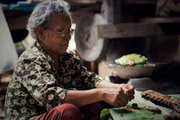 Old woman cooking in Thai kitchen