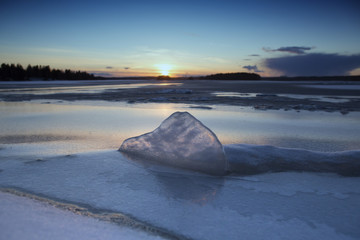 Melted ice block is laying on a rock on a thin ice. Image taken during sunset in Finland.