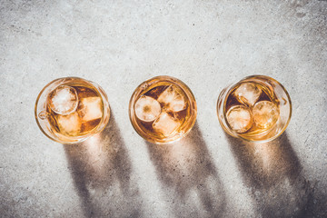 Glasses of whiskey on gray stone table