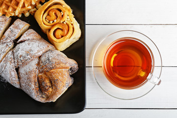 Closeup tea and pastry on white wooden table