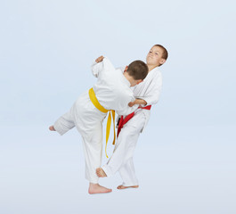 In judogi athletes are training throws on a light background