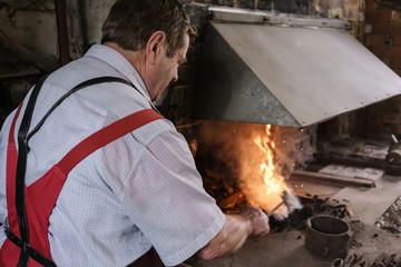 Blacksmith in workshop heating metal in furnace